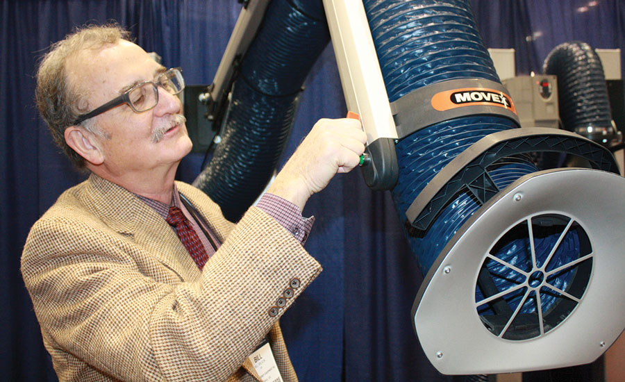 Bill Wilson, a rep with Capital Energy Equipment Inc. in Vienna, Virginia, tests  the flexibility of one of Movex's Fume  Extractor Arms.