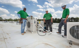 Employees at Raleigh, North Carolina-based Eco Green Air install one of many rooftop condensing units at the Chatham Pointe development in Cary, North Carolina.