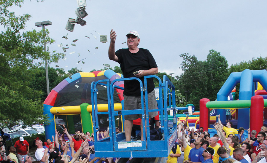 "Dan Jape, CEO of Reliable Heating & Air, Woodstock, Georgia,""makes it rain"" dollars at the company's summer employee party."