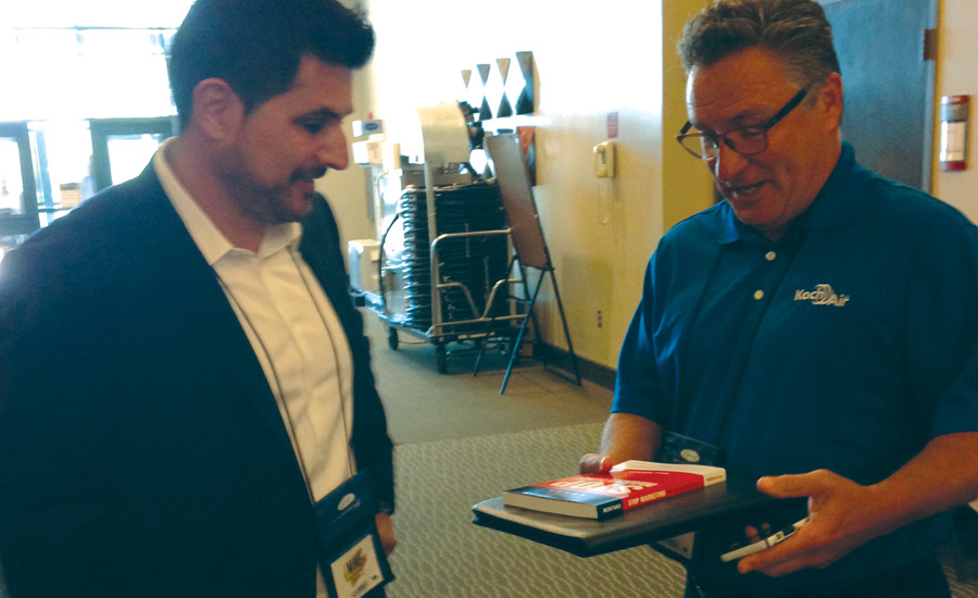 Mike Montano (left), founder of ReviewBuzz, talks with Brian Redman, Koch Air.