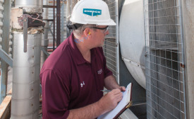 A building engineer examines an LST-style centrifugal cooling tower during a routine maintenance checkup. PHOTO COURTESY OF EVAPCO INC.