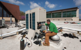 Eco-Green Air installers charge two new VRF units on a church roof. - ACHR