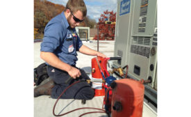 Nick Briggs, service technician, Pleune Service Co., Grand Rapids, Michigan, works on a unit. When it comes to service work, the company uses overtime as a tool to dampen demand during peak times - The NEWS - ACHR