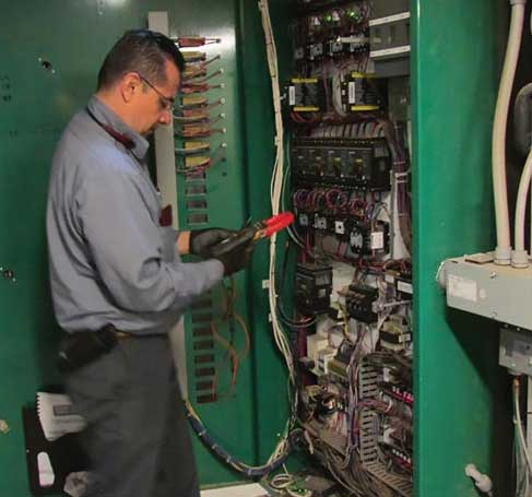 Henry Garcia, a level 8 service technician with CoolSys, troubleshoots a refrigeration system. - The ACHR News