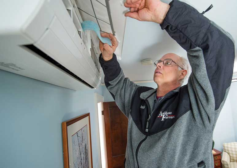 In Minneapolis, an Abbott Ferraro technician sets the washable filter in place as the final stage of this Fujitsu heat pump installation. - The ACHR News