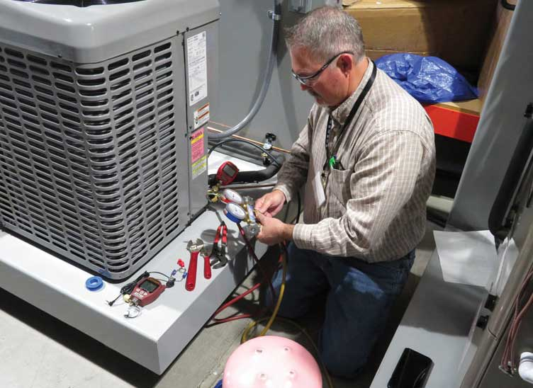 Obtaining accurate measurements from a system, as shown here by Paul Delaware, a UA instructor from Local 469 in Phoenix, can be difficult if it contains mixed refrigerants. - The ACHR News