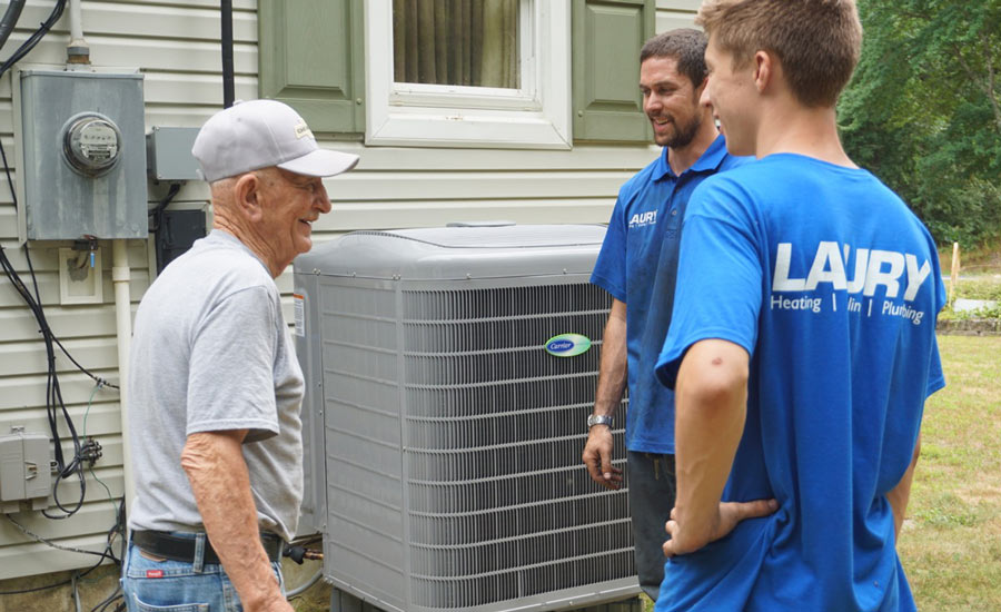 Technicians from Laury Heating, Cooling, Plumbing talk with a homeowner who just purchased a new system. - The ACHR News