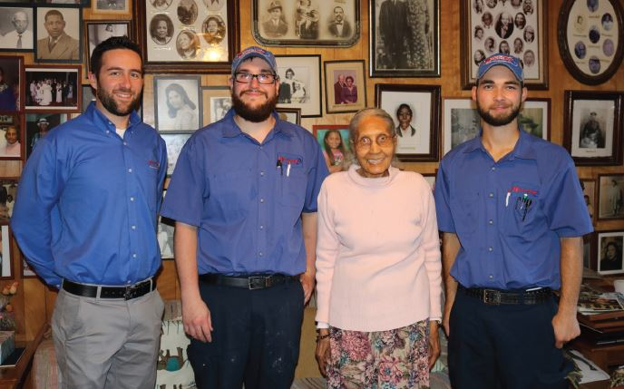 Technicians from Accu-Temp Heating & Air Conditioning Inc., Howell, Michigan, stand with Cora Grant, a program participant. - The ACHR News