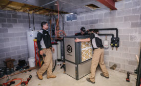 Vertex mechanical technicians move the 4-ton Q Energy ground source heat pump into place during a retrofit. - The ACHR News