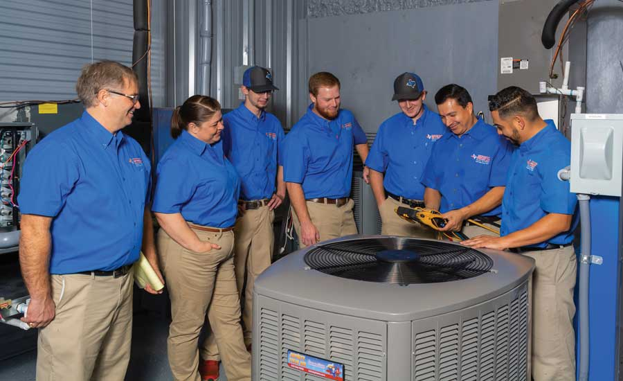 With lead technician Raymond Rodriguez (far right), the team discusses equipment and procedure in the company's live training lab. - The ACHR News