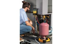 Technician inspecting outside condensing unit. - The ACHR News