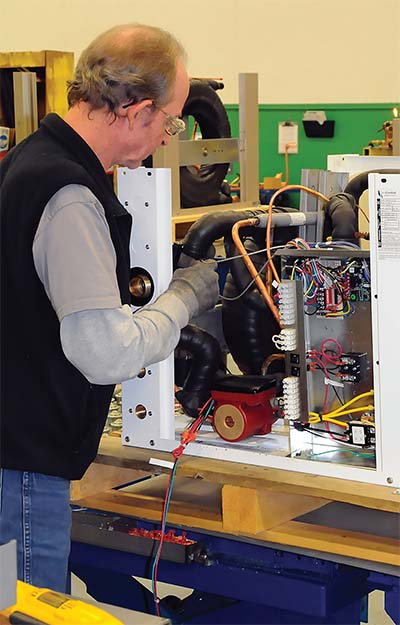 A geothermal heat pump is put together on an assembly line in a factory.
