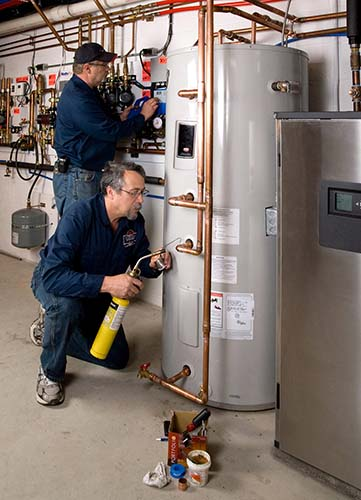 Technicians install a geothermal heat pump.