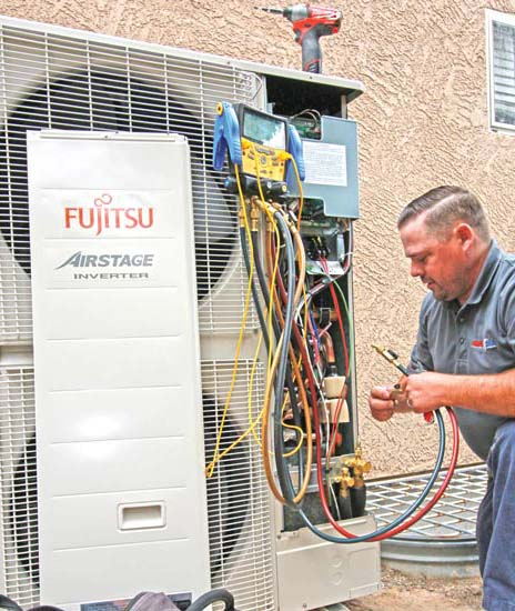 Aaron Sharp of Sharp Air Conditioning & Heating LLC in Mesa, Arizona, checks the refrigerant charge on a single-phase VRF system.