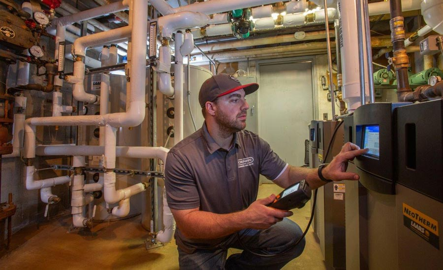 A tech with Dennon Plumbing and HVAC LLC checks the controls on a Laars boiler.