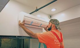 An HVAC tech installs a ductless unit in the ceiling of a Cornish Pasty restaurant.