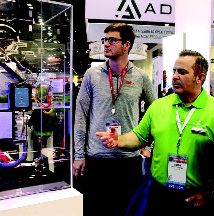Emerson rep Brian Feenie shows off the manufacturer's latest products to an Expo attendee.
