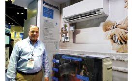Victor Flynn stands next to the ClimaPure XE Series ductless heat pump system.