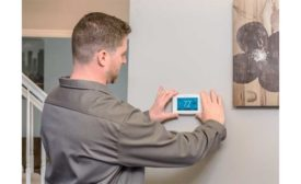 A technician installs a smart thermostat.