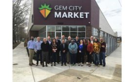 Representatives from Emerson, Chemours, Hussmann, and the Gem City Market board gather in front of the soon-to-open Gem City Market.