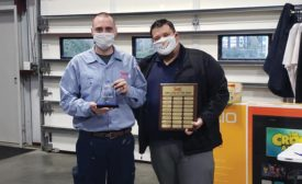 Swift Services installer/tech Josiah Kidman (left) receives the Employee of the Year award from general manager Shane Bedgood.