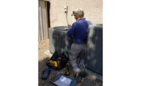 Technician servicing air conditioning equipment.