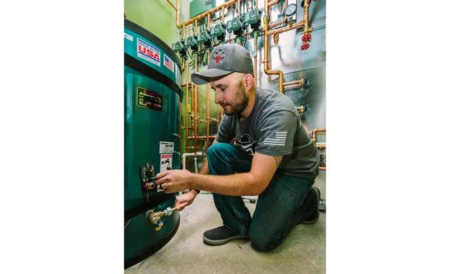 Keefer Rader, owner of Outlaw Mechanical, changes modes on a circulator.