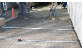 A crew covers a radiant heat system with concrete.