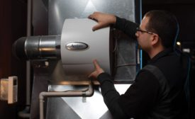 A technician installs the Aprilaire 600 whole-home evaporative humidifier.