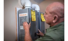 A technician installs a propane-fueled tankless water heater.